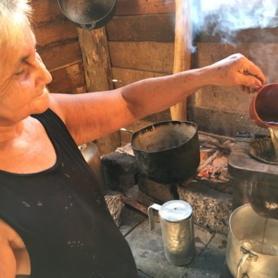 Maria brewing coffee from beans she roasted on the wood fire, and ground by a son with a mortar and pestle.
